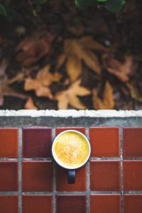 Turmeric latte surrounded by leaves